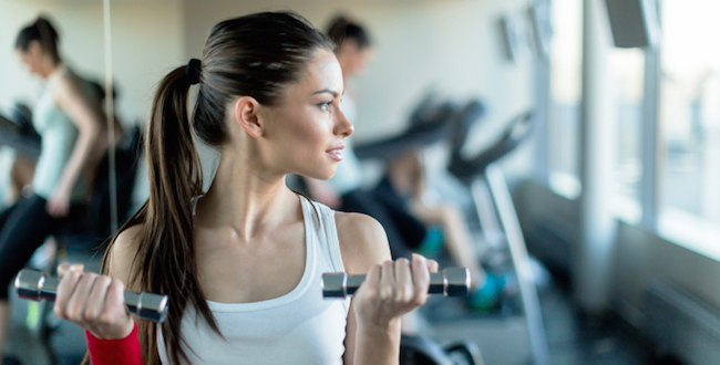 Beautiful, young woman lifting weights in a gym standing next to a mirror
